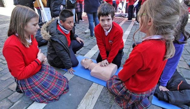 Escolares hace una práctica de reanimación a un muñeco.