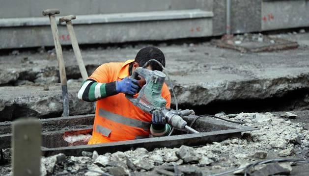 Un trabajador realiza obras en el asfalto de una calle.