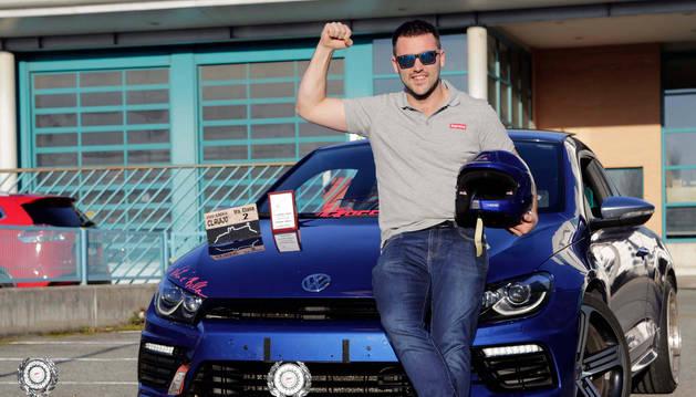 Daniel del Villar posa junto a su coche y sus premios en rallys de montaña.