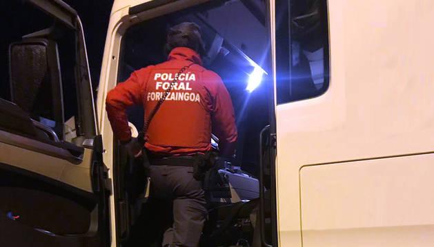 Un agente de la Policía Foral inspecciona la documentación de uno de los vehículos controlados.