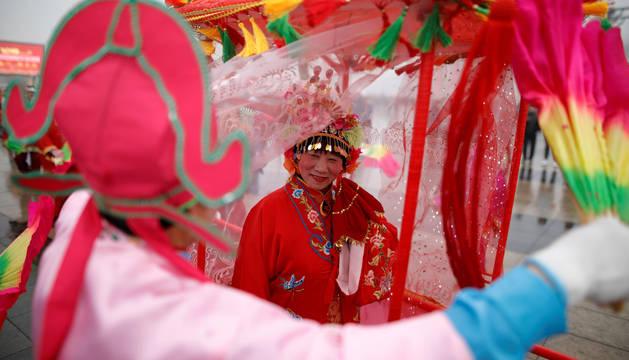 Varias personas vestidas con trajes tradicionales participan en el Festival de las Linternas en Pekín.