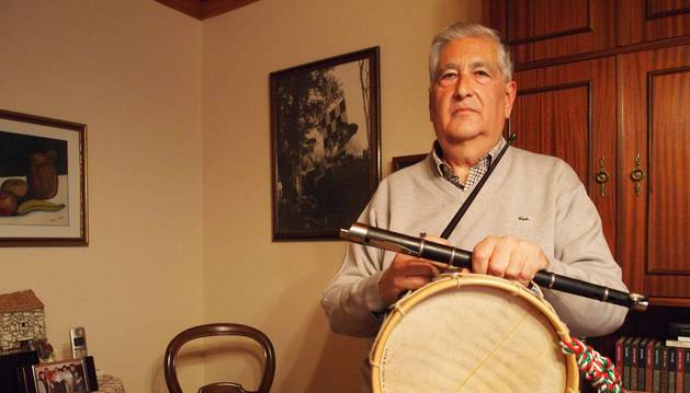 El veterano músico sangüesino Luis María Vital Sevillano posa en su casa junto a su txistu y su tamboril. Tras él, una foto de la antigua Banda de Txistularis de Sangüesa.
