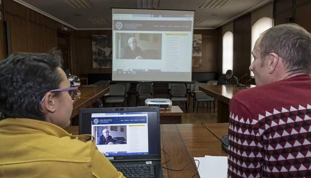 El edil Regino Etxabe e Itziar Luri, de Labrit Patrimonio, muestran la página con uno de los testimonios. En la pantalla, aparece el que fuera secretario municipal de Estella, Carmelo López Estébanez.