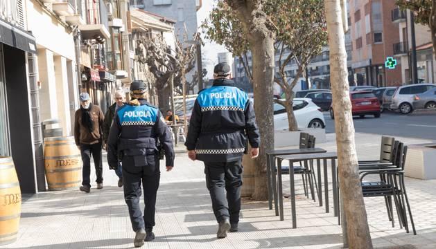 Dos agentes de la Policía Municipal patrullan por la céntrica calle Muro de Tudela.