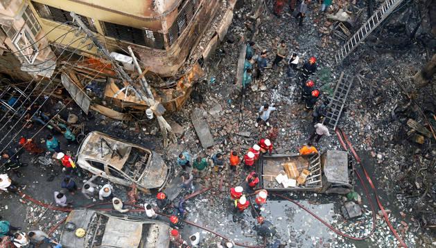 Varios bomberos inspeccionan los escombros tras el incendio declarado en la madrugada de este jueves en el barrio Chawkbazar del casco viejo de Dacca (Bangladesh).