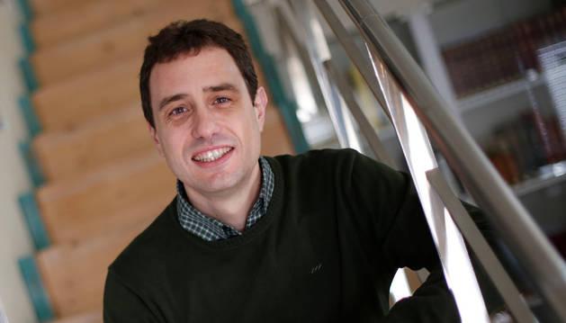 El científico artajonés Jesús Bañales posa para la entrevista sentado en una escalera.