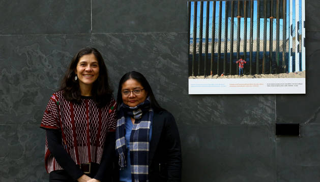 Andrea Villaseñor y Karla Rivas, con una fotografía del periodista Iván Benítez tomada en la valla de Tijuana y que se expone en el Parlamento de Navarra como parte de la muestra 'Stand by: más allá de las fronteras'.