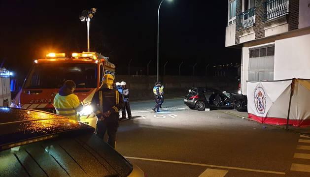 Bomberos junto al coche, en el lugar del accidente.