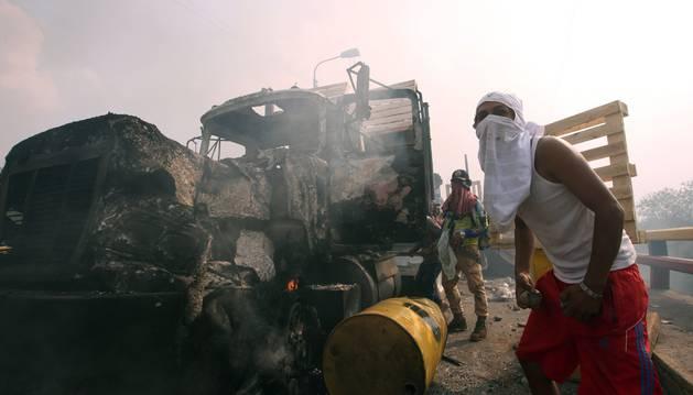 Foto de manifestantes se enfrentan con miembros de la Policía Nacional Bolivariana, junto a un camión quemado.