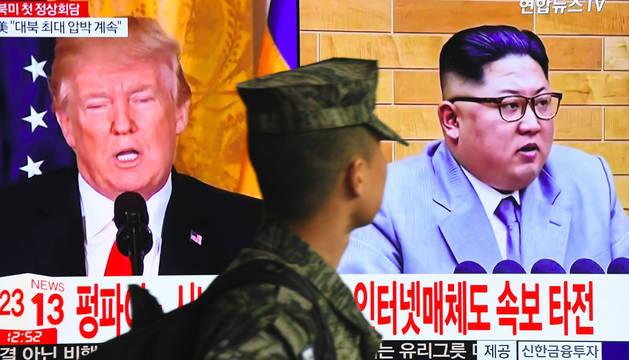 Un soldado surcoreano, frente a una pantalla con Donald Trump y Kim Jong Un en Seúl.