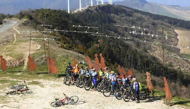 Un grupo de ciclistas se fotografía junto al monumento al peregrino de El Perdón en una soleada jornada.