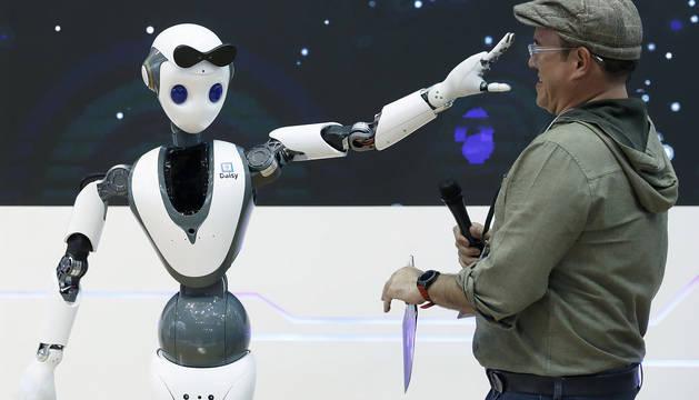 Un robot con tecnología 5G juguetea con uno de las asistentes al Mobile World Congress de Barcelona.
