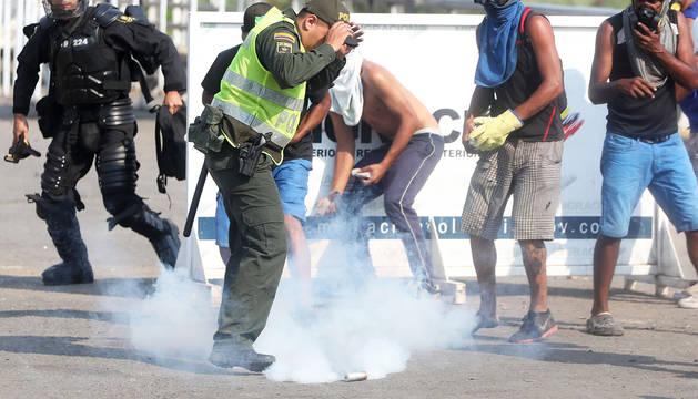 Un policía colombiano junto a un grupo de jóvenes venezolanos que se enfrentan con la Guardia Nacional Bolivariana.