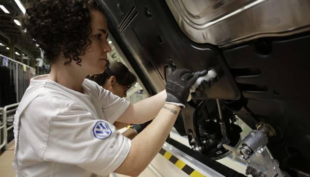 Una operaria de montaje trabaja en el fijado del carenado inferior de un Polo.