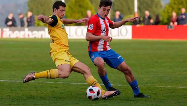 Daniel Sandoval, del Sporting B, protege el balón bajo la presión de Cabrera, del Izarra.