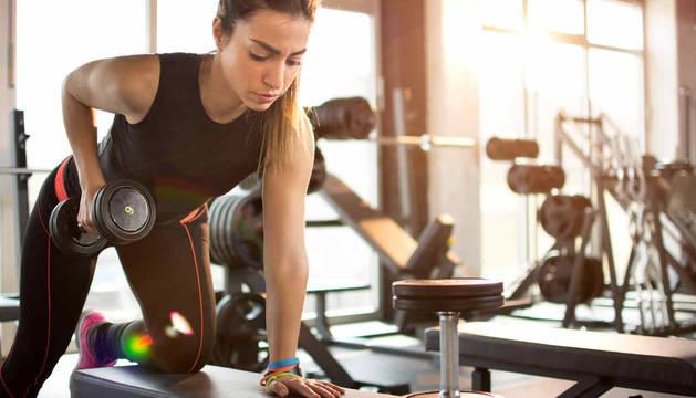 Foto de una joven realiza una serie de ejercicios con pesas en un gimnasio.