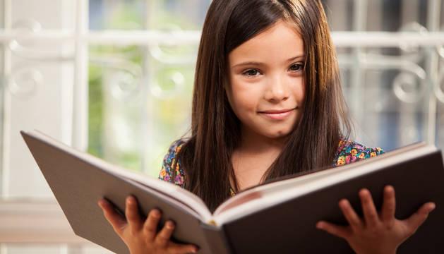 Una niña leyendo un libro.