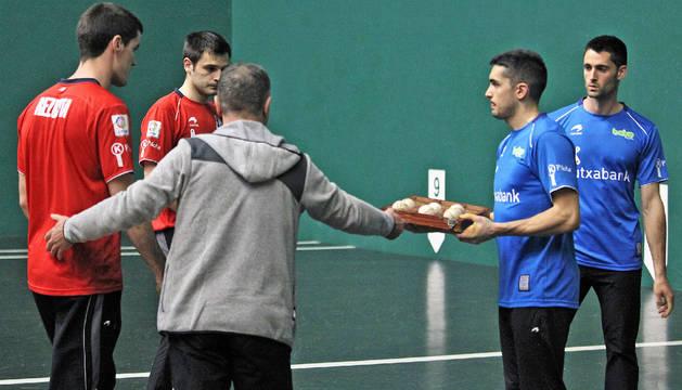 El seleccionador Martín Alustiza entrega a Víctor la caja con las seis pelotas que se pondrán en juego mañana en el Labrit.