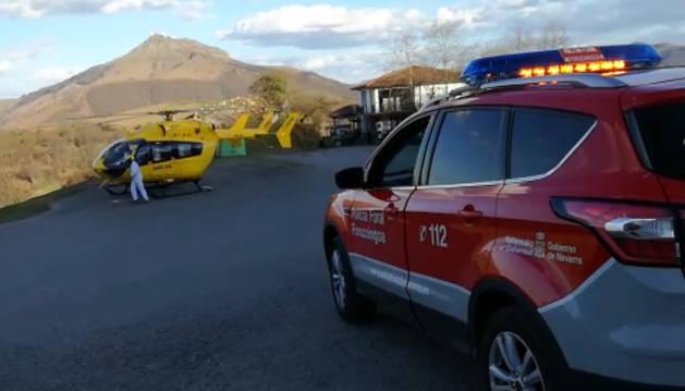 Patrulla de la Policía Foral que atendió el suceso junto al helicóptero que trasladó al herido.