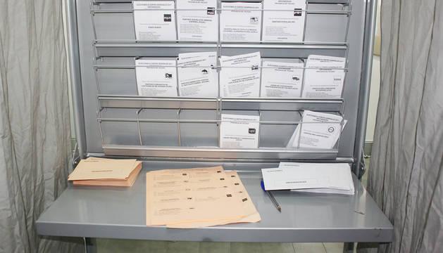 Interior de una cabina con papeletas y sobres para votar.