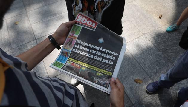 Foto de un hombre lee un diario con titulares sobre el apagón eléctrico en Caracas (Venezuela).