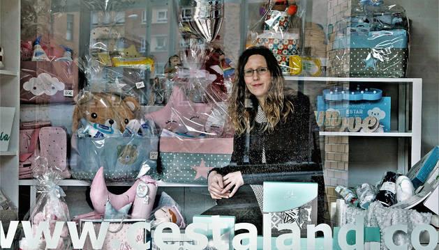 Ana Monente dentro del escaparate, al lado de su farmacia, con las canastillas que prepara para bebés y futuras mamás.