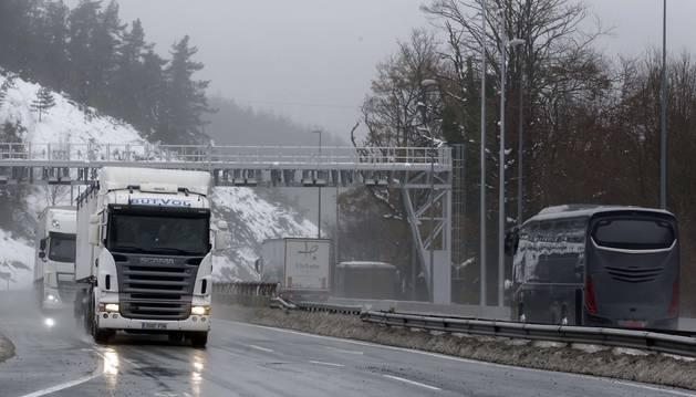 En una imagen de archivo, dos camiones cruzan el pórtico instalado en Etxegarate.
