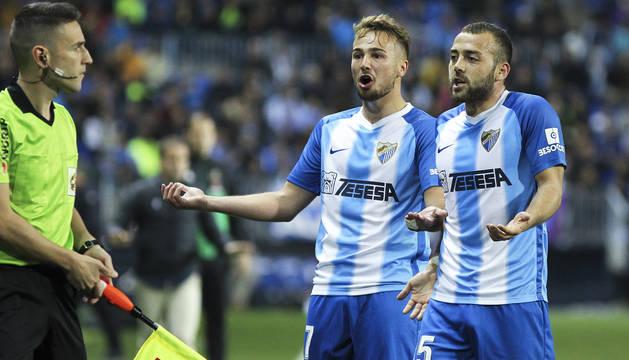 Javier Ontiveros y Keidi Bare protestan al asistente durante un momento del Málaga-Osasuna.
