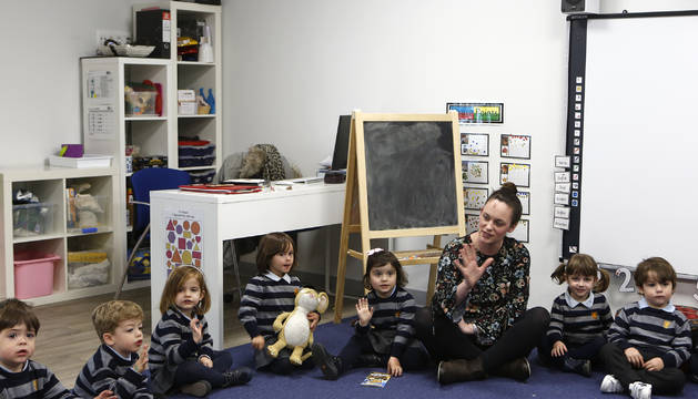 Alumnos de infantil junto a una profesora en una de las  aulas del colegio de Gorraiz.