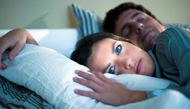Foto de una mujer desvelada en la cama.