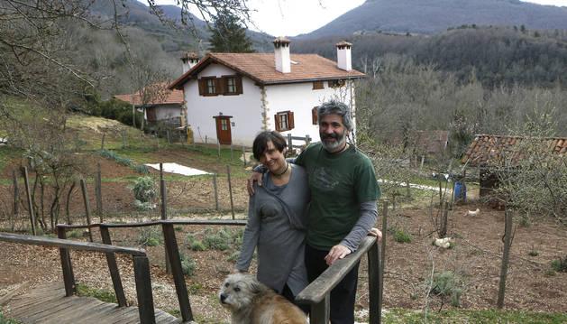 Alicia Mendive y Luismi Montoya, en el acceso a la cabaña en el árbol junto a su casa, al fondo, en Villanueva de Arce.
