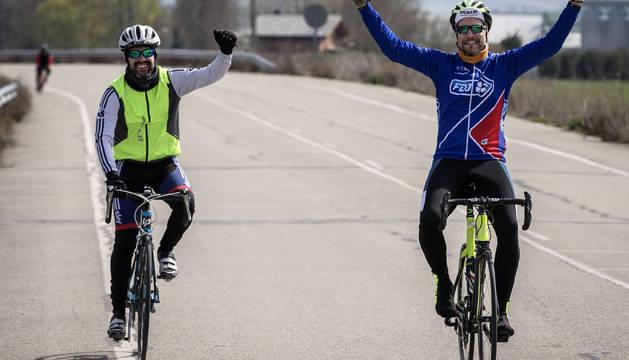 Gesto de victoria y alegría de dos ciclistas en el tramo final de la bajada del puerto de Loiti, en la Javierada.