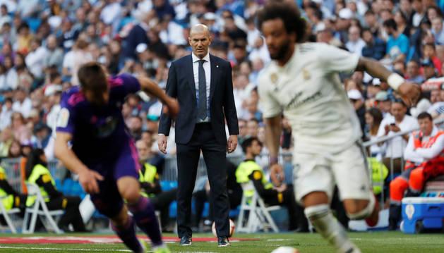 Zinedine Zidane observa cómo Marcelo progresa por su banda junto a un rival.