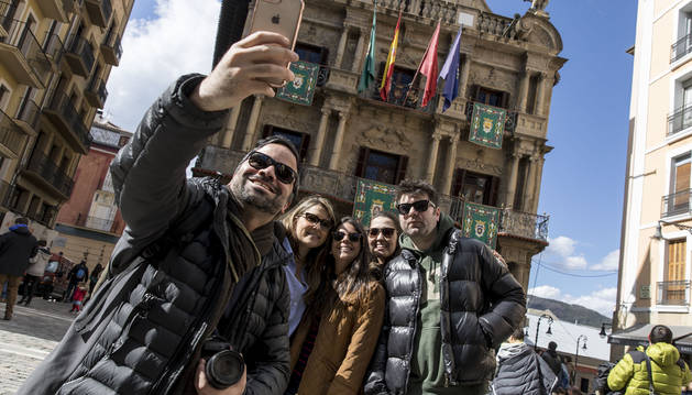 Unos turistas se hacen una foto delante del Ayuntamiento de Pamplona