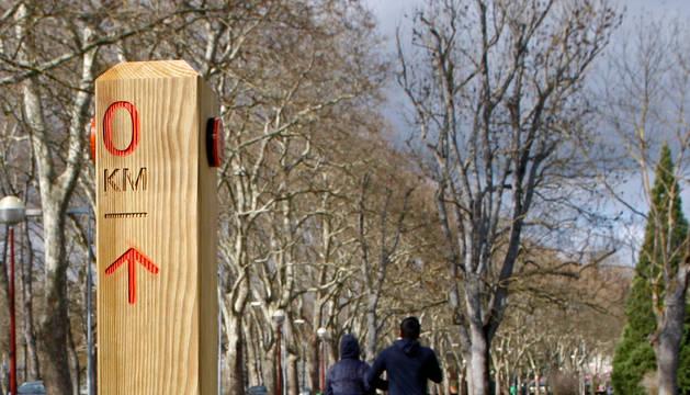 Dos corredores pasan por la salida del nuevo circuito balizado para correr en la Universidad de Navarra.