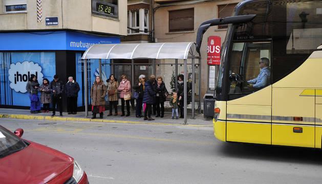 Vecinos esperan en una parada de autobús en Peralta