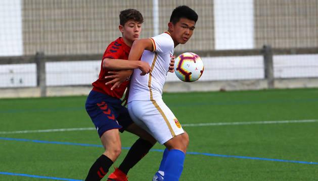 Un componente de la selección china sub-15 protege el esférico ante un jugador de las categorías inferiores de Osasuna.