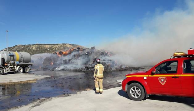 Varios bomberos trabajan en la extinción del incendio que ha afectado a una fábrica de pellets en Zaragoza.