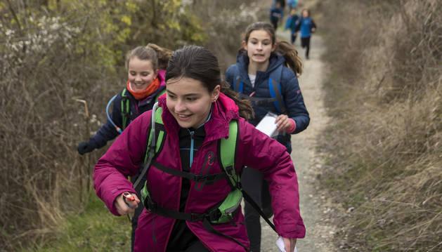 Tres jóvenes deportistas, con el mapa en la mano, corren por los senderos de San Cristóbal-Ezkaba en busca de una de las balizas 'escondidas' que deben localizar con las pistas y por las que deben pasar para puntuar.