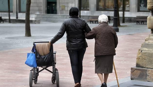 Una persona mayor es acompañada por otra más joven durante el paseo por una plaza.