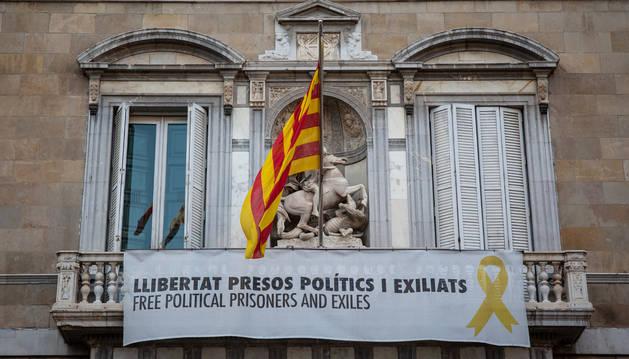 Foto de una pancarta en la fachada de la Generalitat pide la libertad de los 'presos políticos y exiliados'.