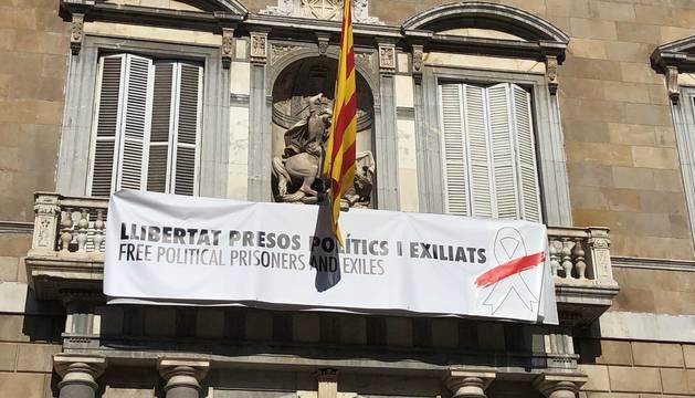 Foto del balcón del edificio de la Generalitat con pancarta con lazo blanco y franja roja por presos políticos.
