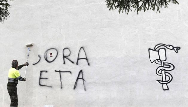 Un trabajador municipal limpia en 2013 una pintada de apoyo a ETA en un edificio de Pamplona.