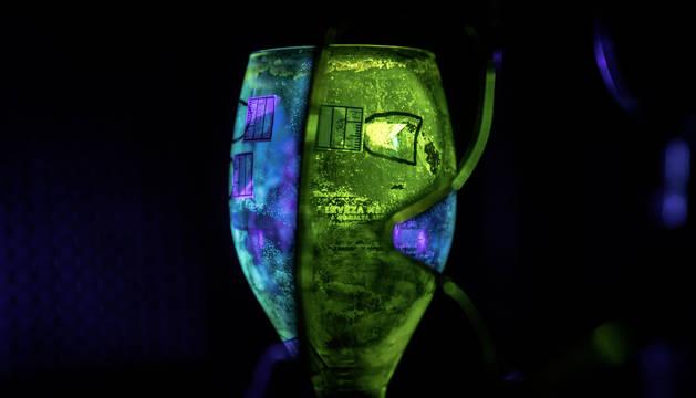 Un agente busca huellas en un vaso de cristal recogido en el escenario de una pelea entre varias personas ocurrida en un bar en Navarra.