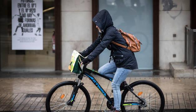 Un ciclista pertrechado para la lluvia circula por una calle de Pamplona.