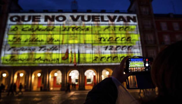 Una persona fotografía uno de los mensajes de los 'papeles de Bárcenas' proyectados en la Plaza Mayor madrileña.