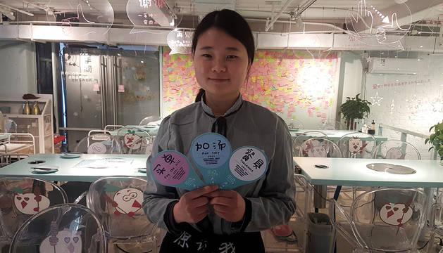 Cao Xueting muestra tres de los carteles que utilizan durante el servicio en el restaurante