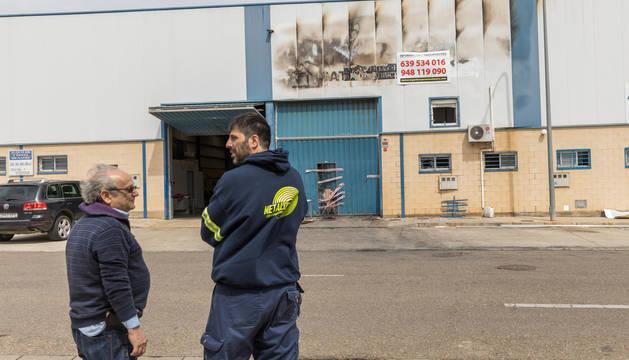 Dos personas charlan frente a la nave de Eventos Lázaro, precintada por la policía mientras dura la investigación.
