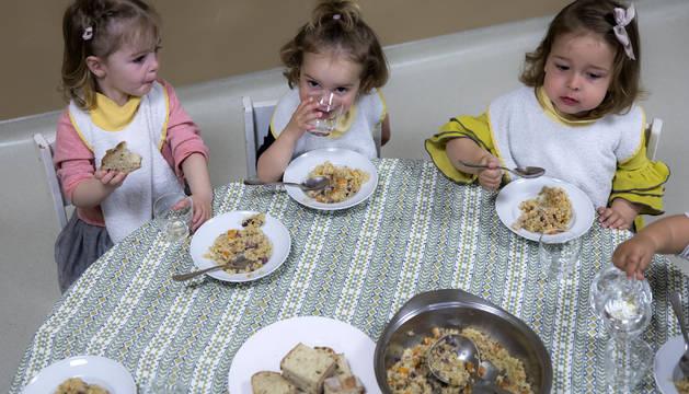Tres niñas comen el plato de arroz y pan en el comedor de la escuela infantil Buztintxuri.