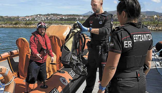 Miembros de la Cruz Roja y de la Ertzaintza, junto a una embarcación del dispositivo.